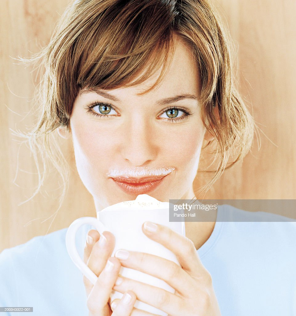 Young woman with froth on upper lip, holding cup, smiling, portrait