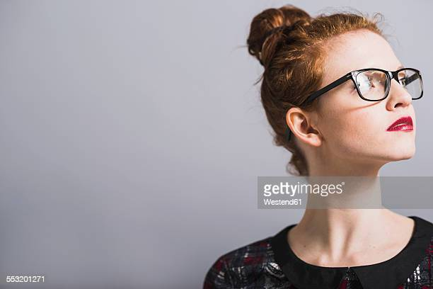 Young woman with glasses and bun looking up
