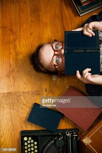 Giovane donna con gli occhiali di nascondersi dietro libro