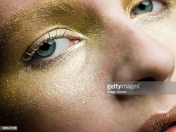 Giovane donna con make-up d'oro sulla superficie