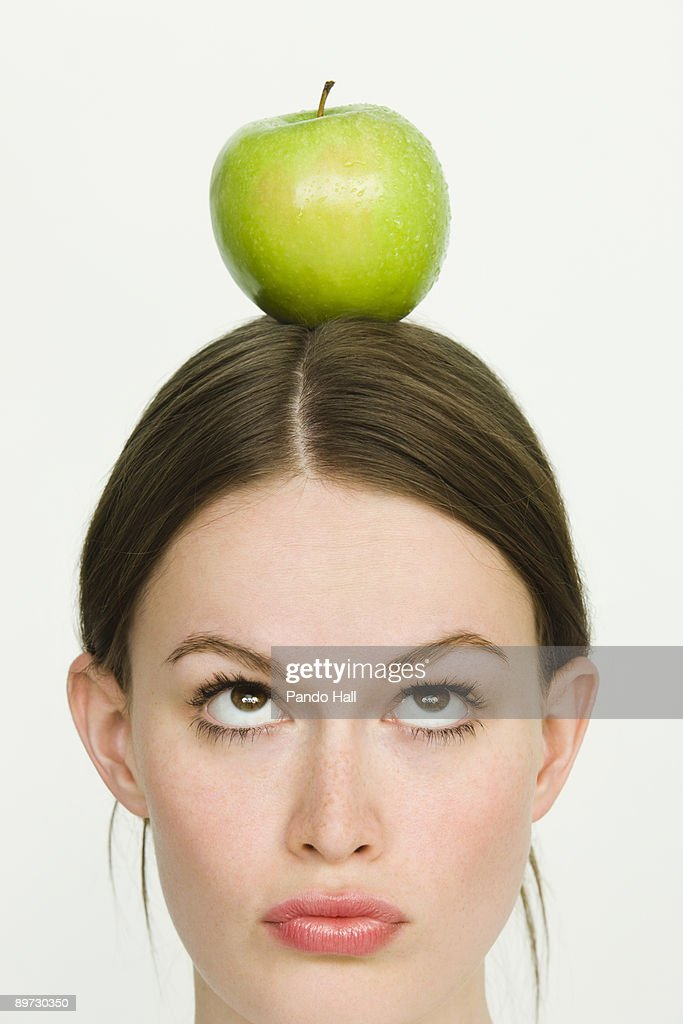 Young woman with green apple on top of head : Stock Photo