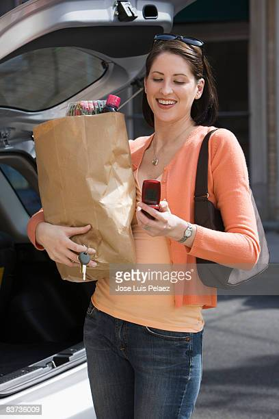 Young woman with groceries checking cell phone