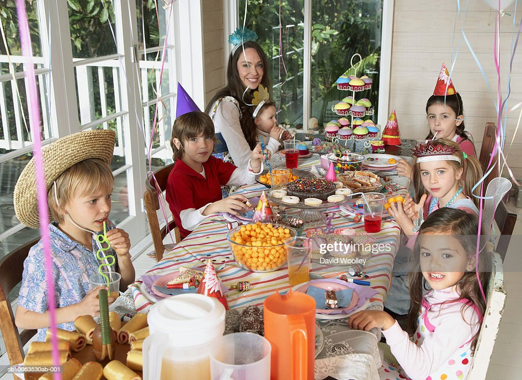 Young woman with group of children (2-7) sitting at table, elevated view : Stock Photo