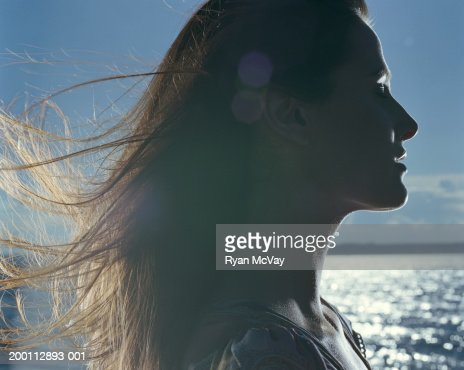 Young woman with hair blowing in wind, profile : Stock Photo
