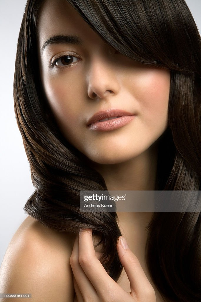 Young woman with hair brushed over eye, close-up, portrait : Stock Photo