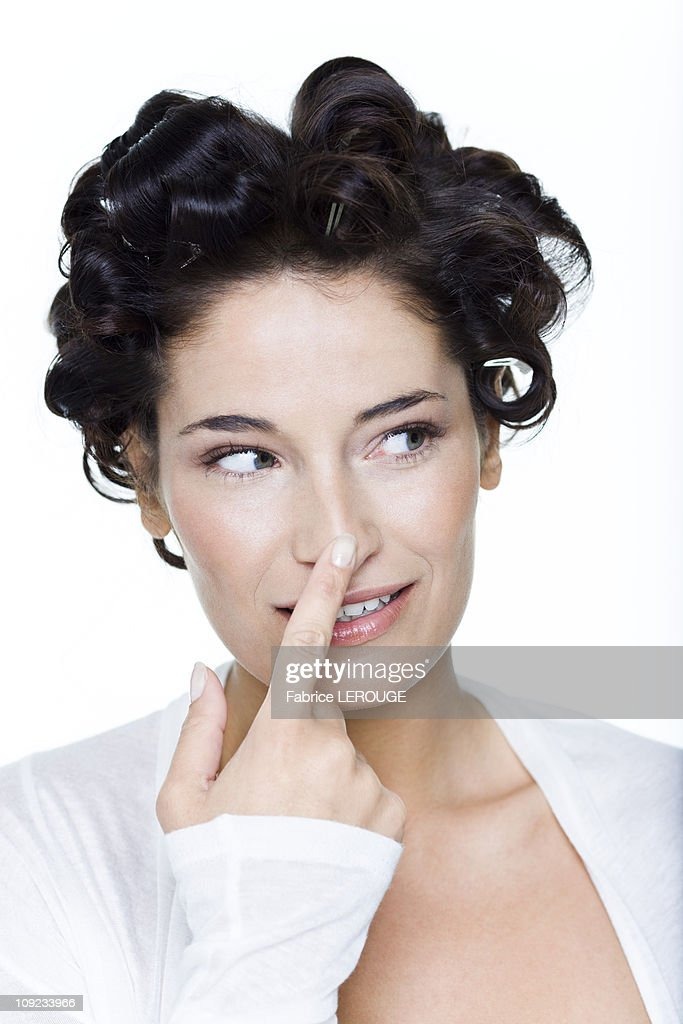 Young woman with hair clips, touching her nose