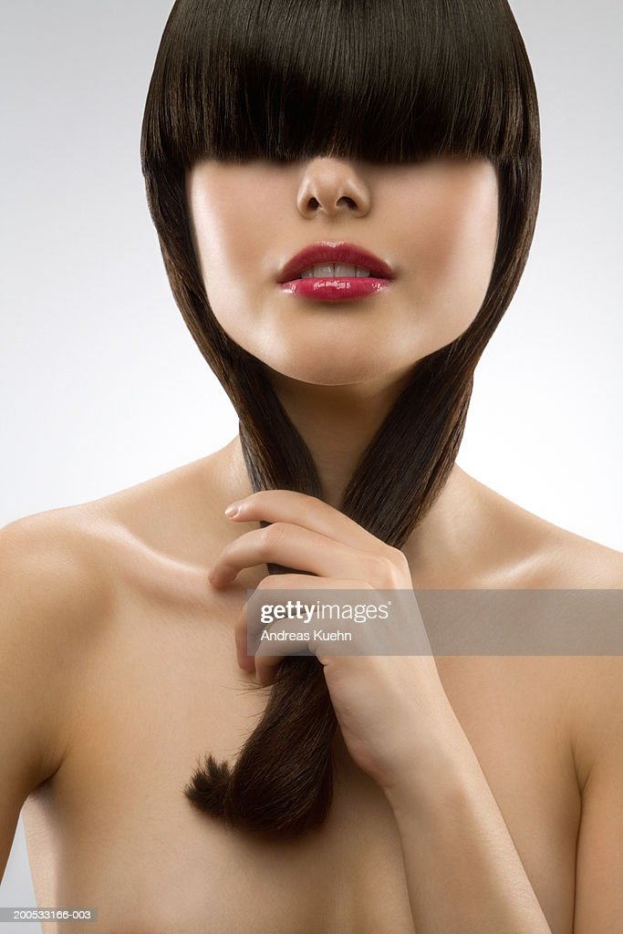 Young woman with hair covering eyes, close-up : Stock Photo