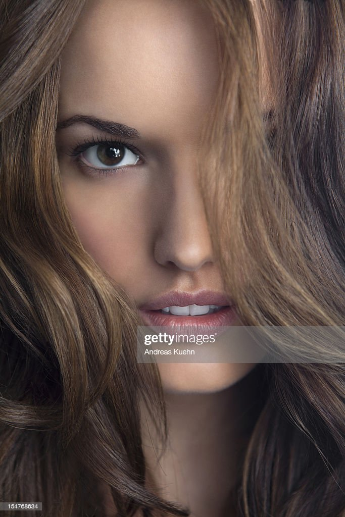 Young woman with hair in front of eye, close up.