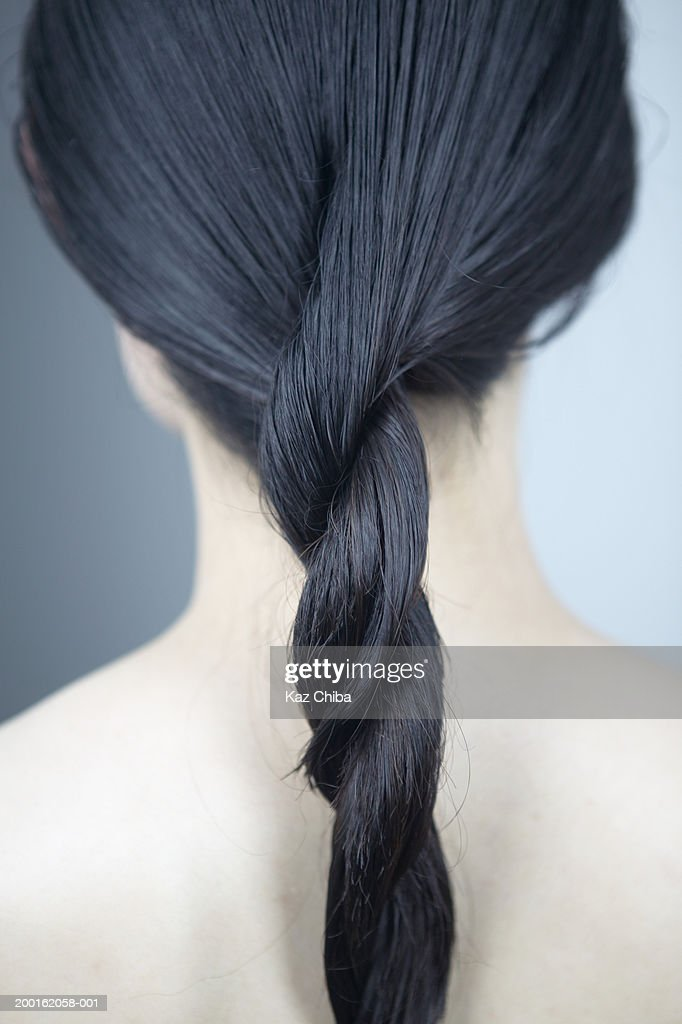 Young woman with hair twisted, rear view : Stock Photo