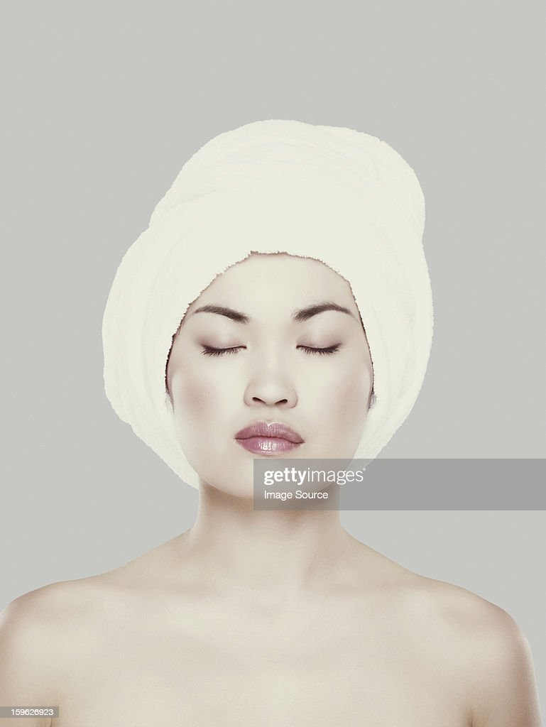Young woman with hair wrapped in towel : Stock Photo