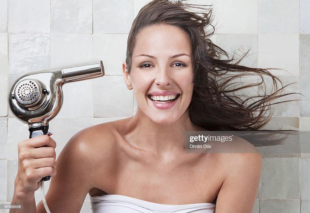 Young woman with hairdryer : Stock Photo
