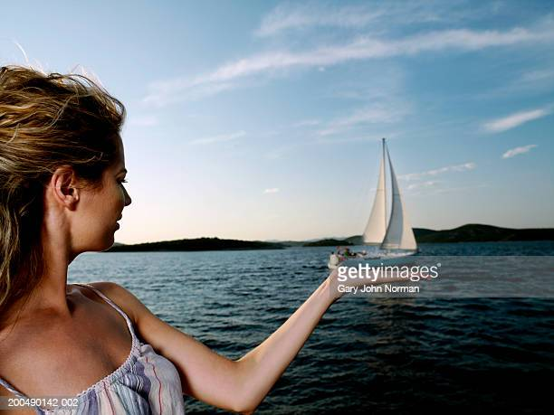Young woman with hand 'beneath' yacht