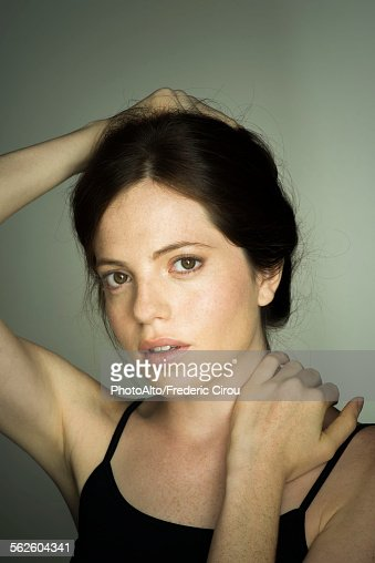 Young woman with hand in hair, portrait