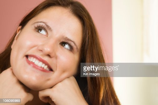 Young woman with hand on chin looking up, close-up : Stock Photo