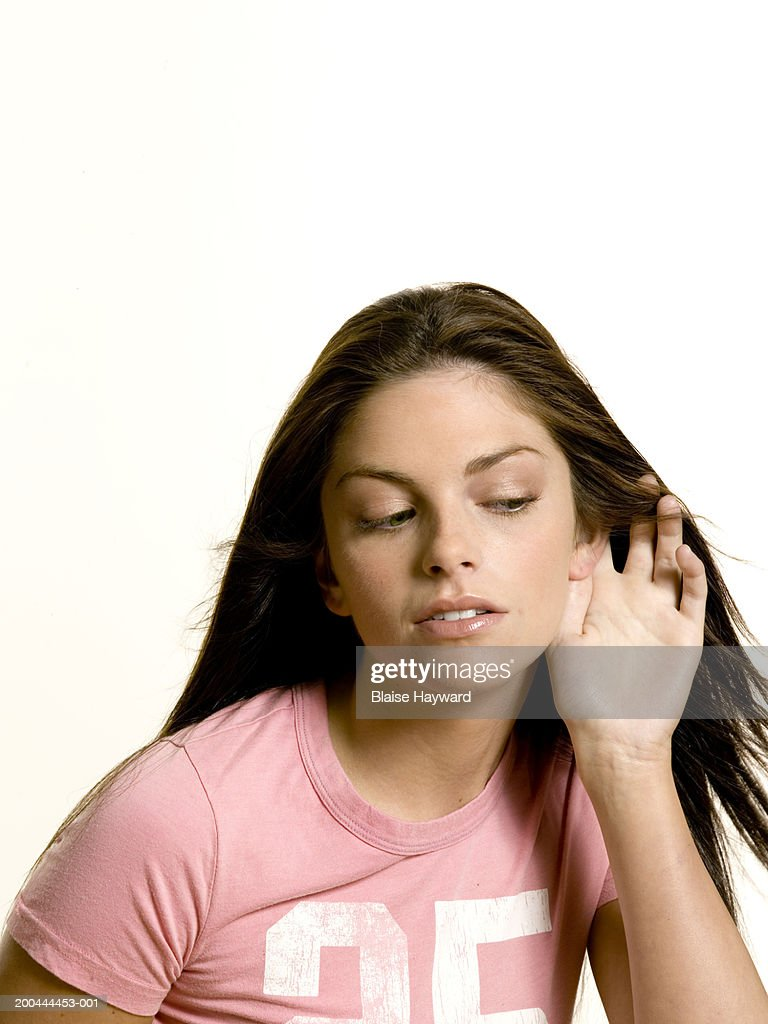 Young woman with hand on ear, looking down : Stock Photo