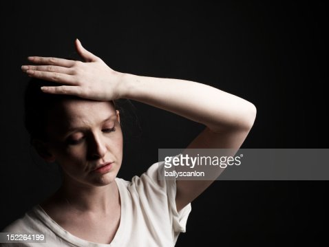 Young Woman With Hand On Head Looking Exhausted. : Stock Photo