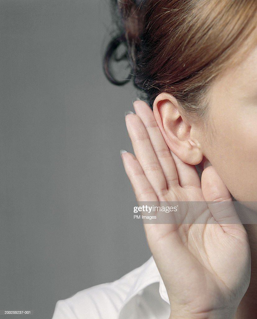 Young woman with hand to ear, close-up : Stock Photo