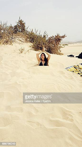 Young Woman With Hands Clasped Buried In Sand