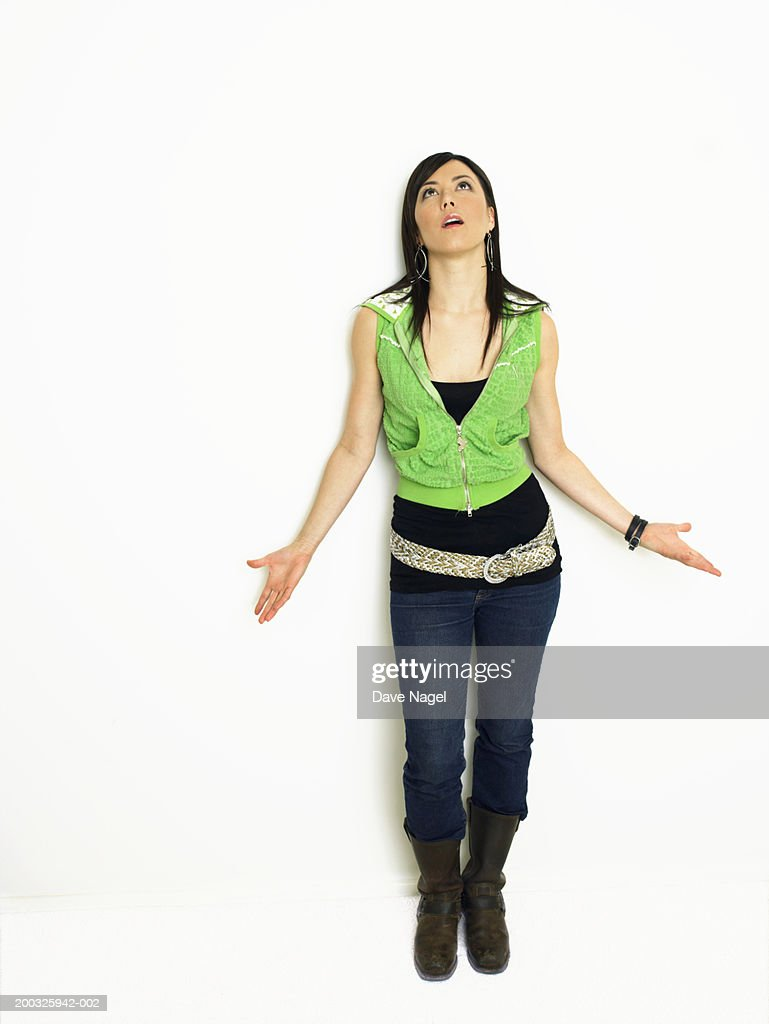 Young woman with hands extended outward looking upward : Stock Photo