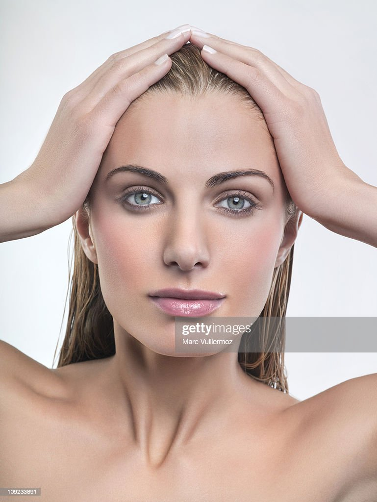 Young woman with hands in hair : Stock Photo