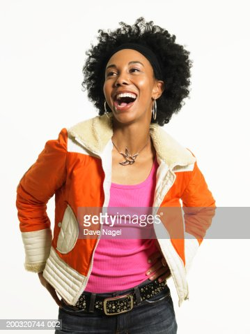 Young woman with hands on hip laughing : Stock Photo