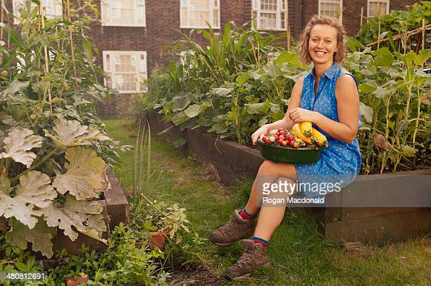Young woman with harvested vegetables on council estate allotment
