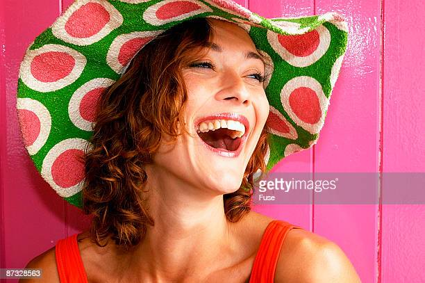 Young woman with hat in front of pink wall