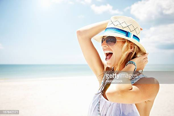 Young woman with hat laughing on the beach