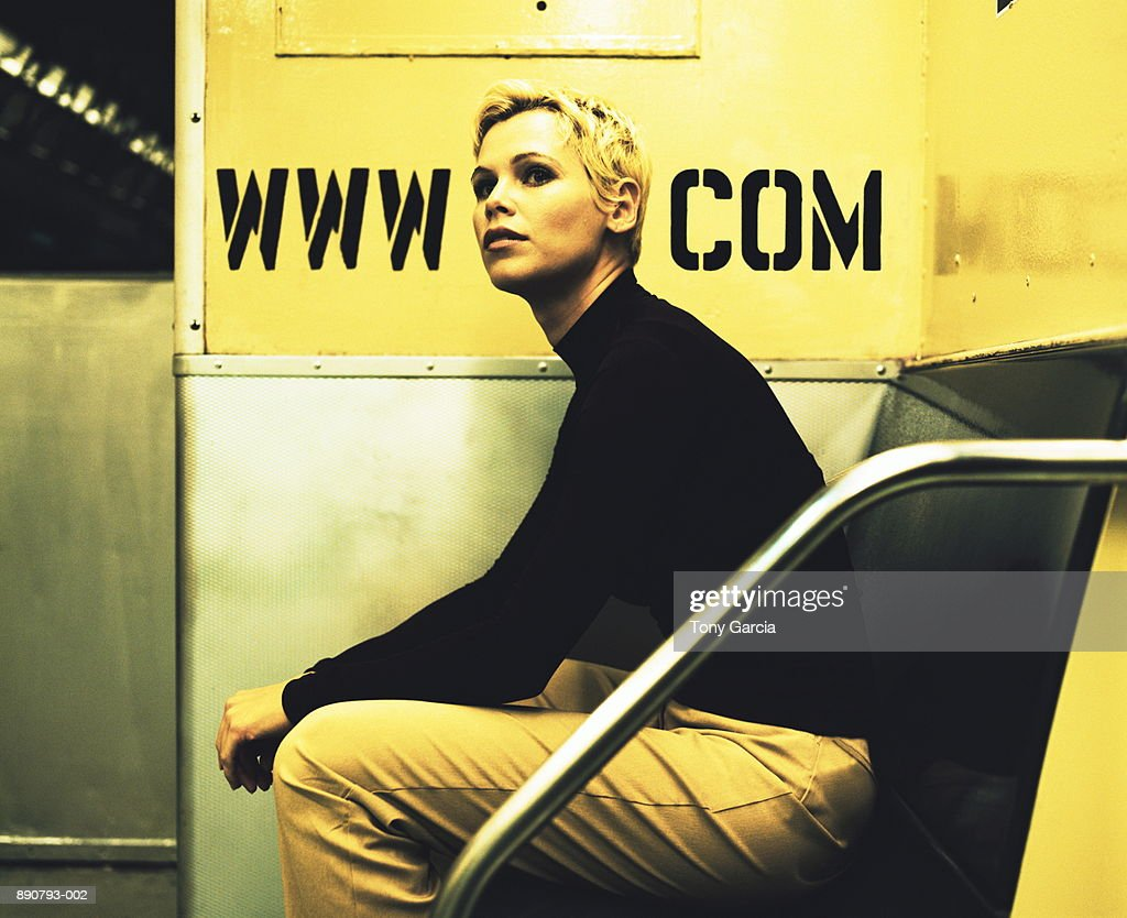 Young woman with head between internet address on subway car wall : Stock Photo