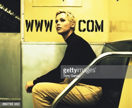 Young woman with head between internet address on subway car wall : Foto de stock