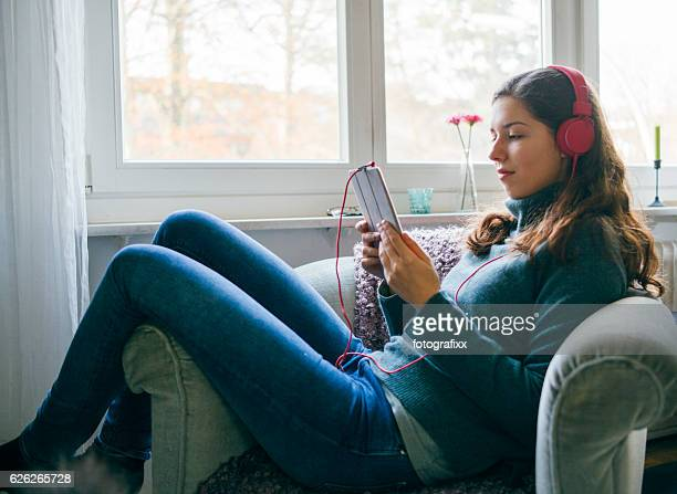 young woman with headphone relax in armchair, looks into touchpad