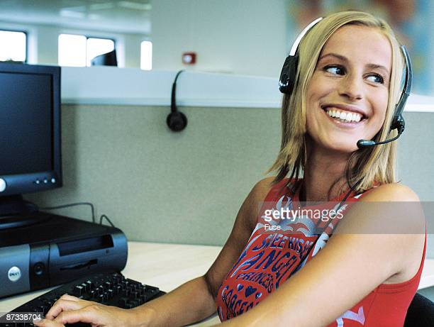 Young woman with headset, using computer