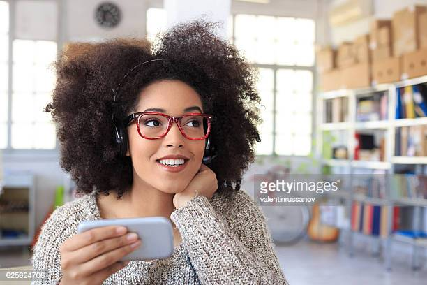 Young woman with headset using smart phone at workplace