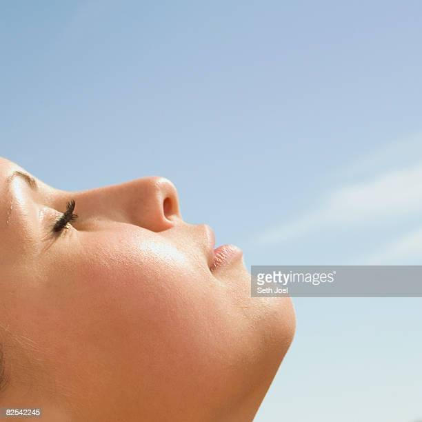 Young woman with her face turned to the sun