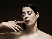 young woman with her finger glued to her face
