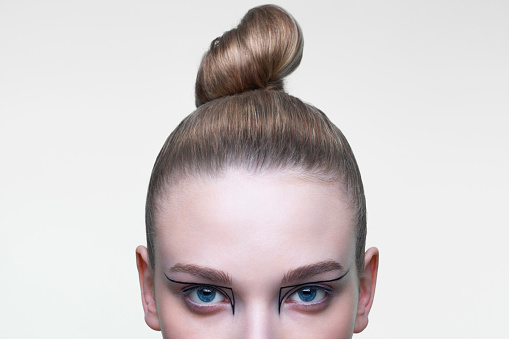 Young woman with her hair in a tight bun, cropped.