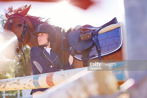Young woman with horse on show jumping course