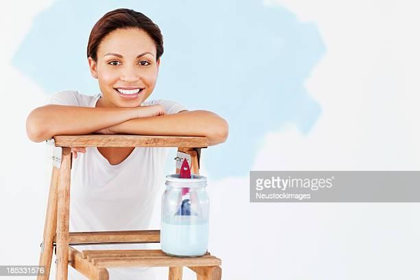 Junge Frau mit Leiter und Farbe Container