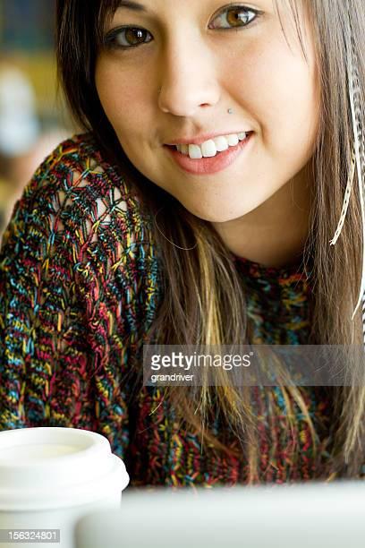 Jeune femme avec ordinateur portable et café à emporter