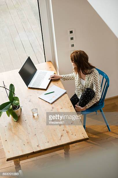 Young woman with laptop at wooden table