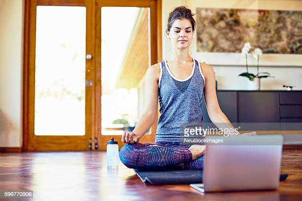 Young woman with laptop in lotus position at home
