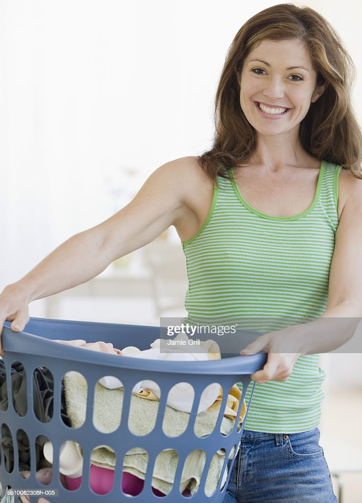 Young woman with laundry basket, smiling : Stock Photo