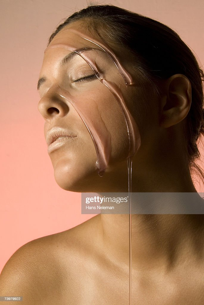 Young woman with liquid dripping from face : Stock Photo