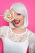 Young cheerful woman with bob hair holding lollipop