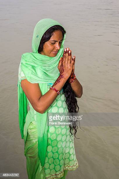 RISHIKESH UTTARAKHAND INDIA A young woman with long black hair henna painted hands and a green dress is praying at the ghats of the holy river Ganges