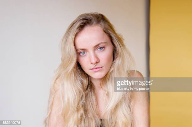 A young woman with long blond hair, clear complexion and no make-up.