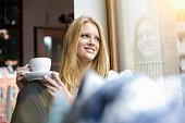 Young woman with long blond hair sitting holding coffee cup, looking away smiling