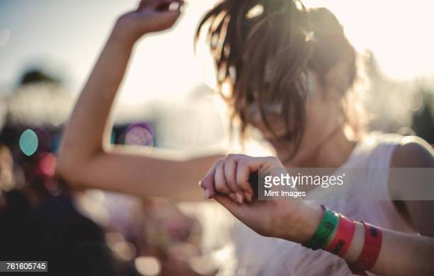 Young woman with long brown hair at a summer music festival dancing.
