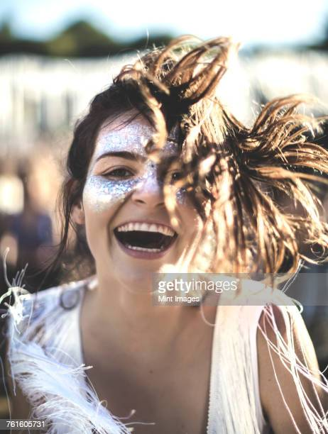Young woman with long brown hair at a summer music festival face painted, smiling at camera.