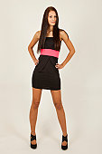 Young woman with long brown hair, black dress and high heels posing standing